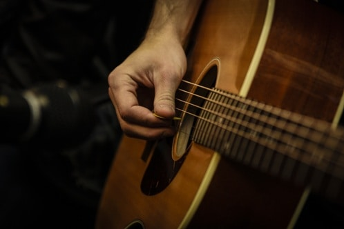 Musician and acoustic guitar practicing live music